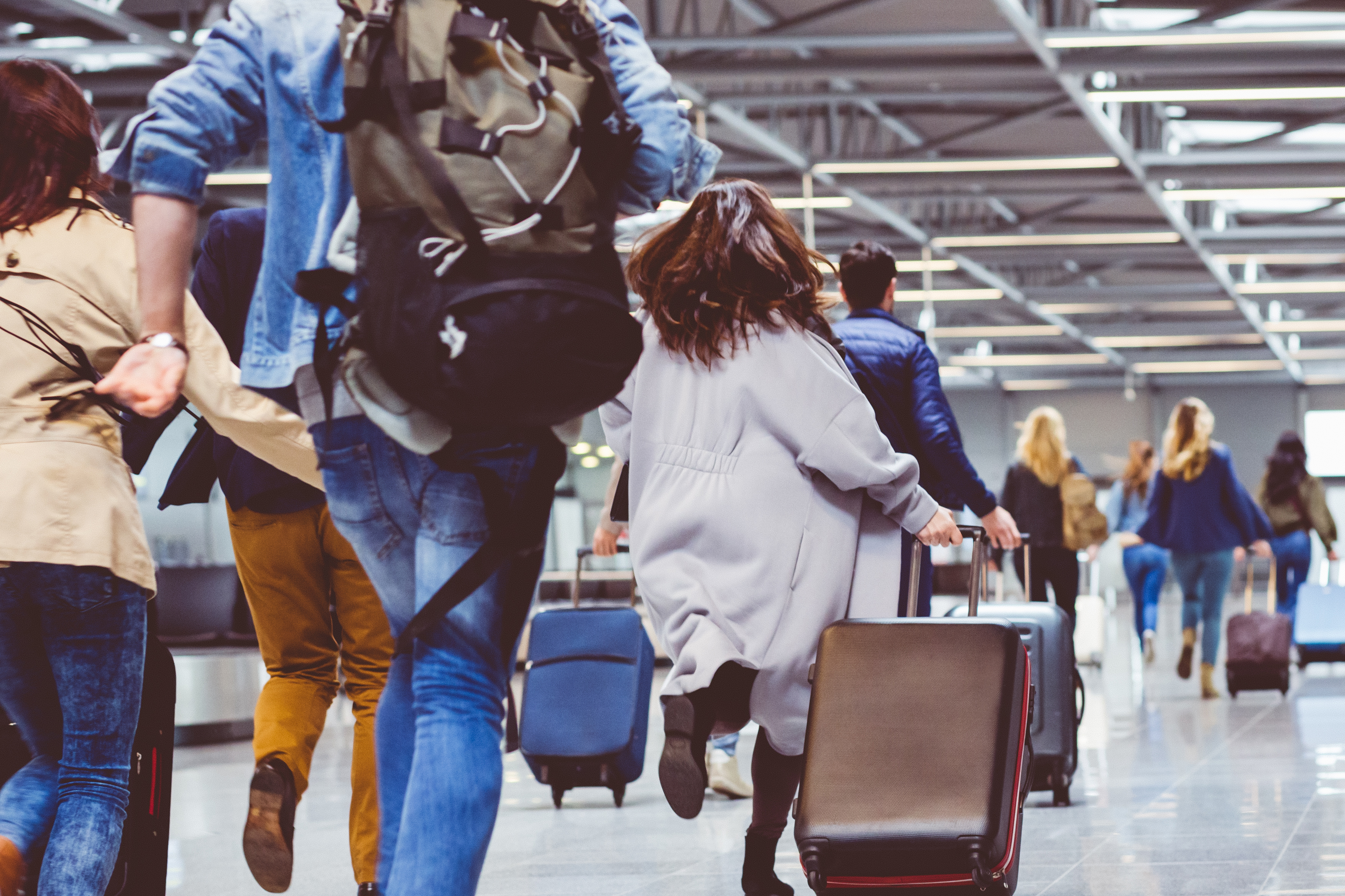 Woman in grey coat running through airport
